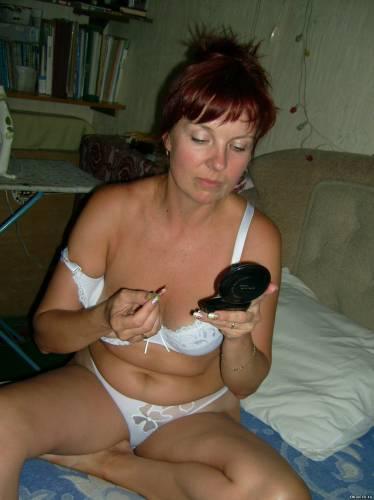 Фото девушек - Женщина сидит на кровати и делает макияж
