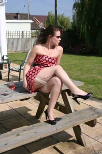 Фото девушек - В коротком платье и в чулках на столе